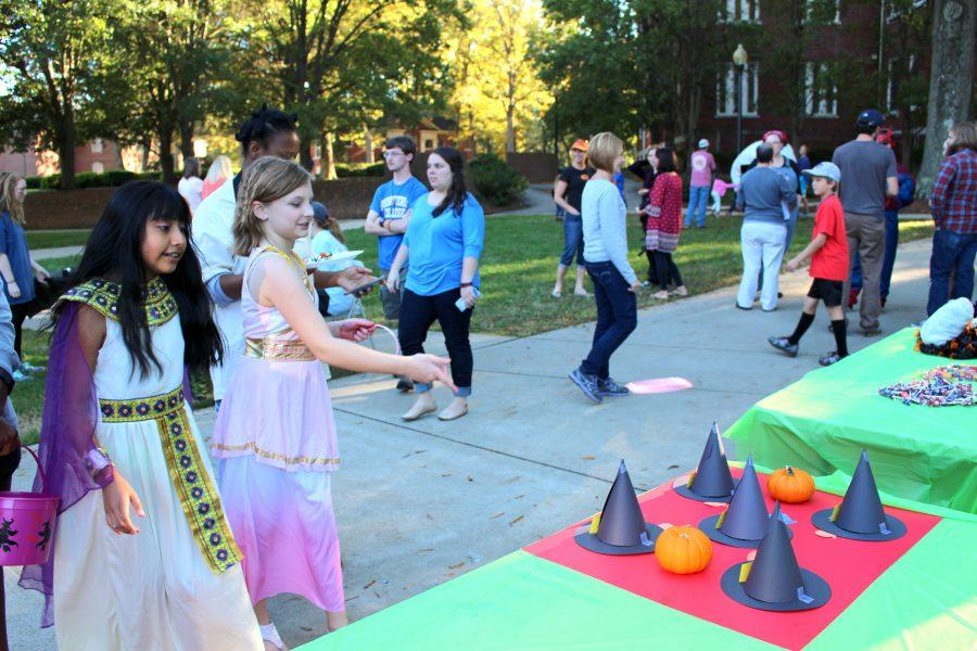 Children play witch hat ring toss at the BlueStocking table.