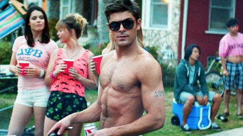 "Photo of Zac Efron in ""Neighbors."" He is grilling and wearing sunglasses."