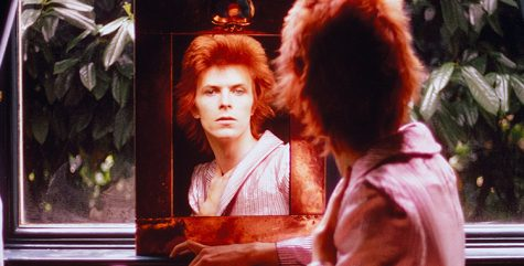 Photo of David Bowie gazing into a mirror.