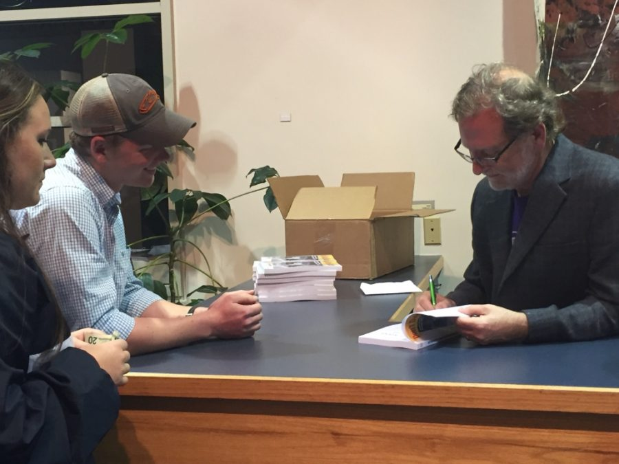 Photo of Barr signing a book